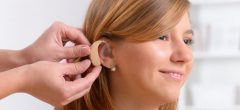 Woman having bluetooth hearing aids fitted