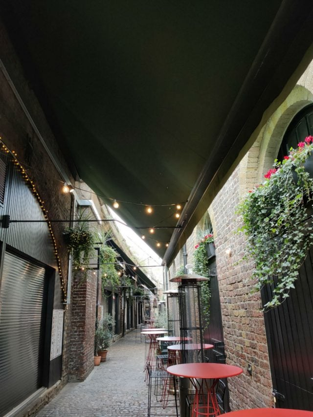 photo of alleyway with tables and shopfronts