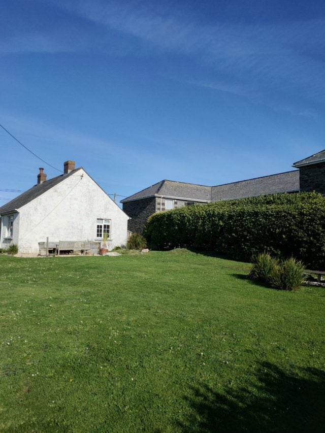 cottage in the sun with green grass and blue sky