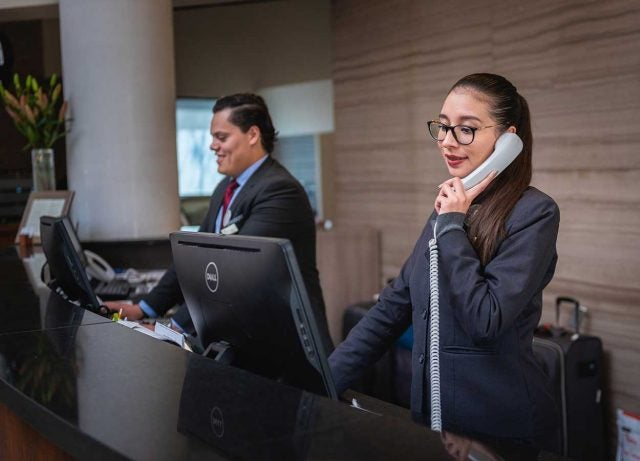 hotel receptionist with phone